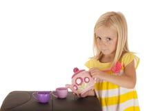 Jeune fille blonde chérie jouant avec un service à thé Image libre de droits