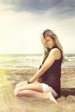 Jeune fille blonde détendant sur le sable de plage Vent dans ses cheveux blonds photos libres de droits