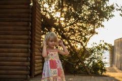 Jeune fille blonde d'enfant ajustant des cheveux extérieurs Lumière chaude de coucher du soleil Le voyage d'été de famille vacati Images libres de droits