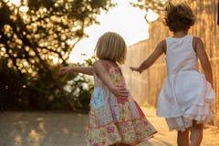 Jeune fille blonde d'enfant avec l'ami ou la soeur courant loin Lumière chaude de coucher du soleil Vacances de voyage d'été de f Photographie stock
