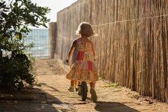Jeune fille blonde d'enfant dans la robe jouant avec le petit vélo d'équilibre Lumière chaude de coucher du soleil Vacances a de  Photos stock