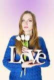 Jeune fille blonde dans le chandail bleu avec amour décoratif de mot Photographie stock