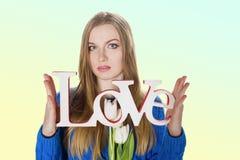 Jeune fille blonde dans le chandail bleu avec amour décoratif de mot Photos stock