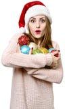 Jeune fille blonde en tant que chapeau du ` s de Santa avec des boules de Noël Images stock