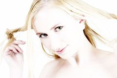 Jeune fille blonde jouant avec son cheveu Images libres de droits