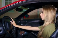 Jeune fille blonde le soir conduisant une voiture de sport photo stock