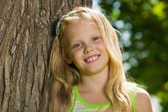 Jeune fille blonde près d'un arbre Photos stock