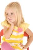 Jeune fille blonde s'asseyant dans la pensée de chaise Photos libres de droits