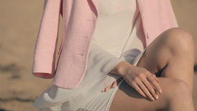 Jeune fille bouclée élégante dans la robe blanche près du banque de vidéos
