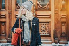 Jeune fille bouclée blonde avec le rétro appareil-photo de film, hiver images stock