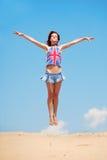 Jeune fille branchant sur un fond de ciel bleu Images libres de droits
