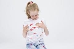 Jeune fille caucasienne active avec les paumes colorées malpropres Fabrication des handprints Photos libres de droits