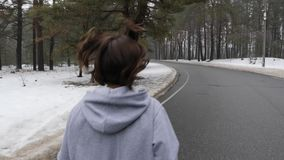 Jeune fille caucasienne attirante courant en parc neigeux en hiver avec des ?couteurs La fin vers le haut du dos suivent le tir banque de vidéos