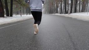 Jeune fille caucasienne attirante courant en parc neigeux en hiver avec des ?couteurs La fin vers le haut du dos suivent le tir M banque de vidéos