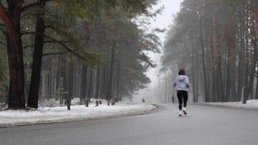 Jeune fille caucasienne attirante courant en parc neigeux en hiver Tir statique arri?re Mouvement lent banque de vidéos
