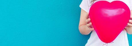 Jeune fille caucasienne de femme dans les prises blanches de T-shirt dans le ballon à air rose de forme de coeur de mains sur le  images libres de droits