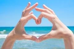 Jeune fille caucasienne de femme faisant le coeur avec des paumes de mains Mer de turquoise avec le fond d'horizon de ciel bleu d Images stock