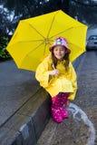 Jeune fille caucasienne jouant sous la pluie Photographie stock