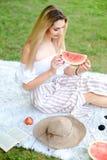 Jeune fille caucasienne mangeant la pastèque, se reposant sur le plaid près des fruits et du chapeau avec l'herbe à l'arrière-pla photo stock