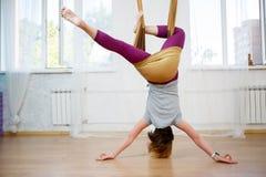 Jeune fille caucasienne posant le yoga aérien avec l'hamac dans la classe Photos libres de droits