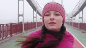 Jeune fille caucasienne potel?e courant sur un pont L'avant suivent le tir Mouvement lent ?quipement pourpre banque de vidéos