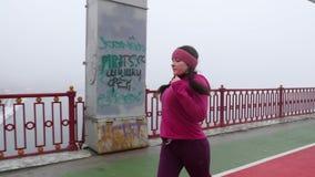 Jeune fille caucasienne potel?e courant sur un pont Projectile lat?ral ?quipement pourpre banque de vidéos