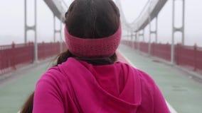 Jeune fille caucasienne potel?e courant sur un pont Suivez de retour le tir Mouvement lent ?quipement pourpre clips vidéos