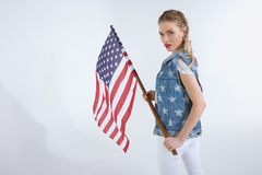 Jeune fille caucasienne regardant l'appareil-photo et ondulant le drapeau des Etats-Unis Photo stock
