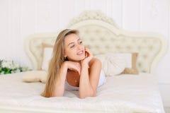 Jeune fille caucasienne se trouvant sur le lit dans le matin, T-shirt blanc de port Photos stock