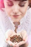 Jeune fille caucasienne tenant le tas des grains de café ininterrompus et du B Image libre de droits