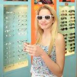 Jeune fille choisissant des lunettes Image libre de droits