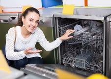 Jeune fille choisissant la nouvelle machine à laver la vaisselle dans le magasin d'électro-ménagers Photographie stock