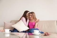 Jeune fille chuchotant le secret personnel dans son oreille d'amis Photo libre de droits
