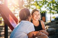 Jeune fille chuchotant un secret à une autre fille Photographie stock libre de droits
