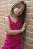 Jeune fille contre un mur de briques Images libres de droits