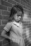 Jeune fille contre un mur de briques Image stock
