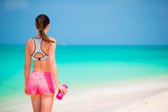 Jeune fille convenable avec la bouteille de l'eau sur la plage blanche Photos stock
