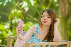 Jeune fille coréenne heureuse et attirante d'étudiant au jardin de station de vacances prenant la photo de selfie avec la caméra  photo stock