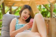 Jeune fille coréenne heureuse et attirante d'étudiant au jardin de station de vacances de vacances utilisant l'appli d'Internet s photographie stock