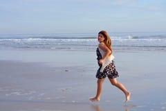 Jeune fille courant sur la plage Photo stock