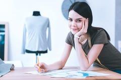 Jeune fille créant de belles robes photos stock