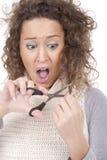 Jeune fille criarde essayant de couper son cheveu Photos libres de droits