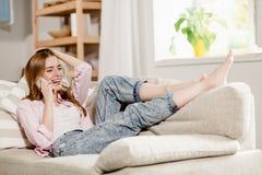 Jeune fille détendant à la maison, se trouvant sur le divan, parlant avec l'ami au téléphone Images libres de droits