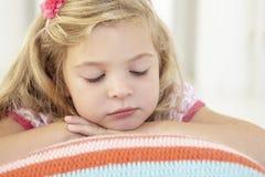 Jeune fille détendant sur le coussin sur le plancher dans la chambre à coucher images stock