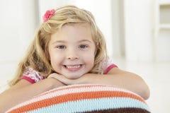 Jeune fille détendant sur le coussin sur le plancher dans la chambre à coucher photographie stock