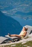 Jeune fille détendant sur une chaise longue en montagnes Dachstein Krippenstein en Autriche Image libre de droits