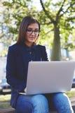 Jeune fille d'étudiant en verres se reposant sur le banc de campus tandis qu'instrument d'ordinateur portable d'utilisation penda image stock