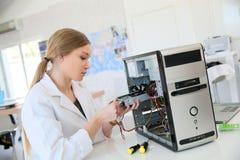 Jeune fille d'étudiant fixant l'unité de disque dur Images libres de droits