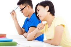 Jeune fille d'étudiant pensant dans la classe avec des camarades de classe Image stock