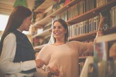 Jeune fille d'étudiants prenant le livre dans la bibliothèque et ayant le conver Images stock